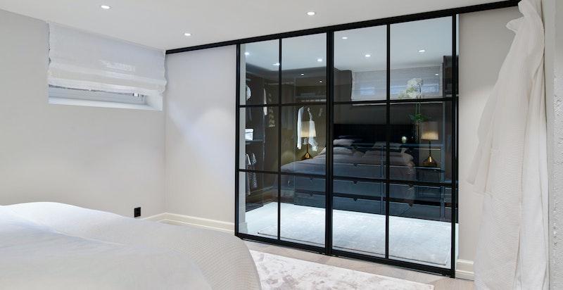Lekre glassdører mellom soverom og walk-in-garderobe.