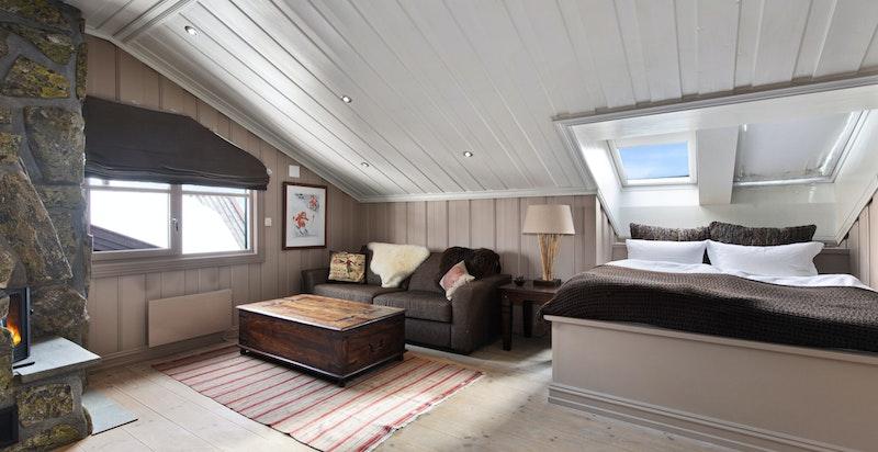 Soverom/loftstue med plassbygget dobbelseng og peis
