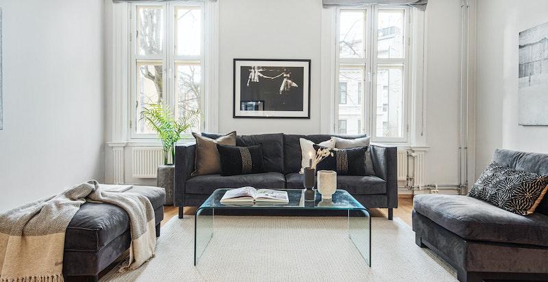 Romslig stue med store vinduer og god takhøyde.