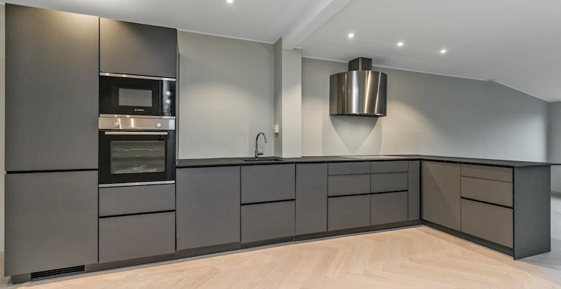 Moderne eksklusivt kjøkken med integrerte hvitevarer og god benk- og oppbevaringsplass