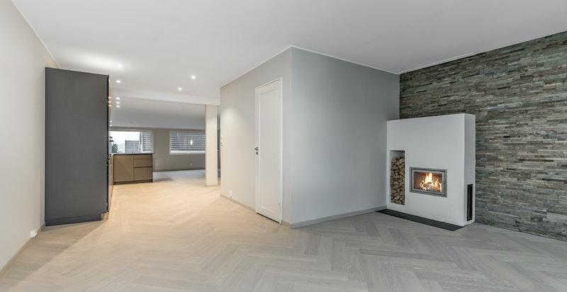 På motsatt side har du en lun og fin stue med store vindusflater og en innbygget vedovn som varmer godt