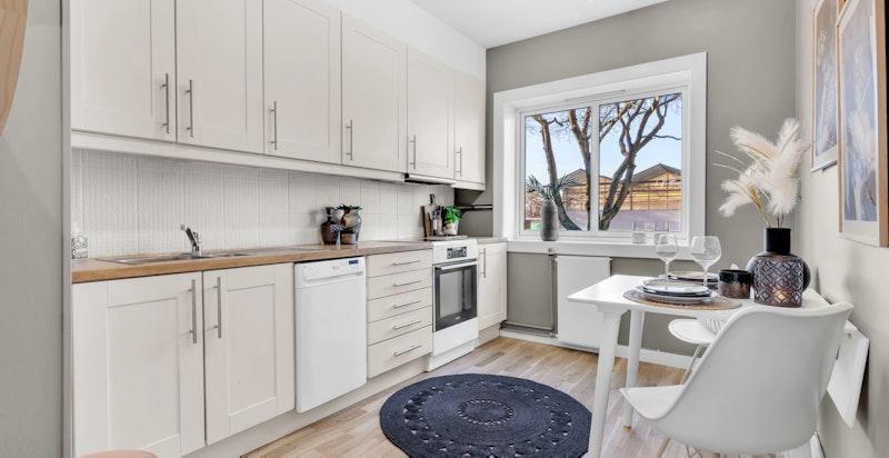 Adskilt kjøkken med hvite glatte fronter kombinert med heltre benkeplate.