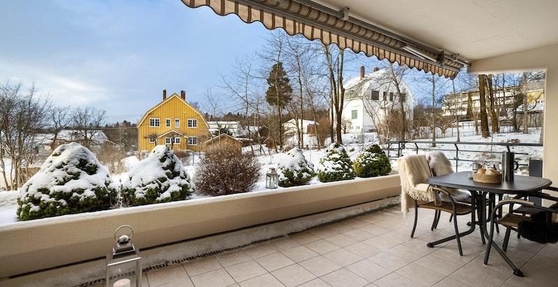 Stor og solrik flislagt terrasse på 14 kvm med elektrisk markise