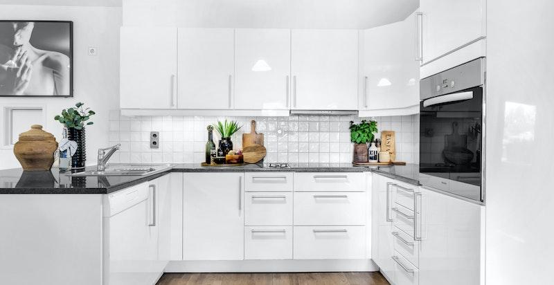 Kjøkkenet er praktisk designet med gode arbeidsflater og skapplass.