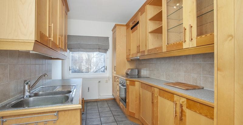 Kjøkken med integrerte hvitevarer og rikelig med skap- og benkeplass
