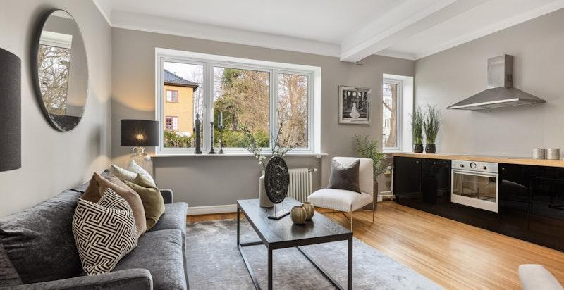 De store vindusflatene kombinert med god takhøyde gjør stuen rommerlig og lys