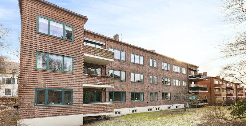 Klassisk teglsteinsgård i funkisstil omkranset av grønne fellesområder