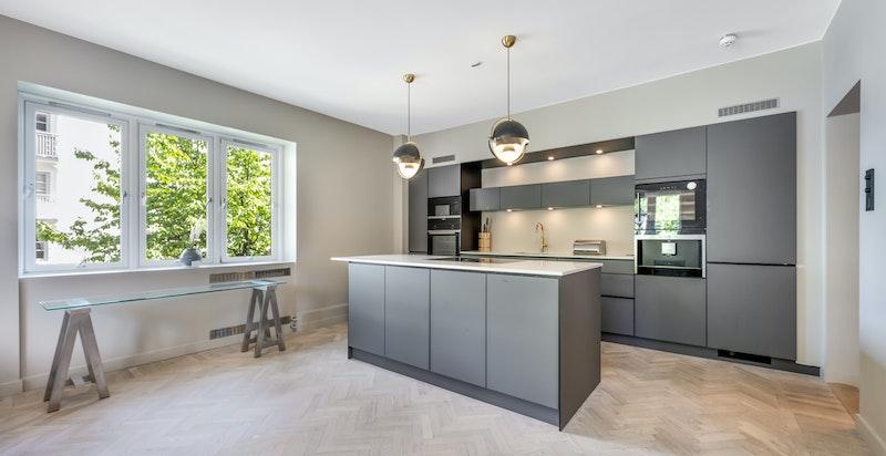 Leiligheten har et moderne åpent kjøkken med integrerte hvitevarer og kjøkkenøy