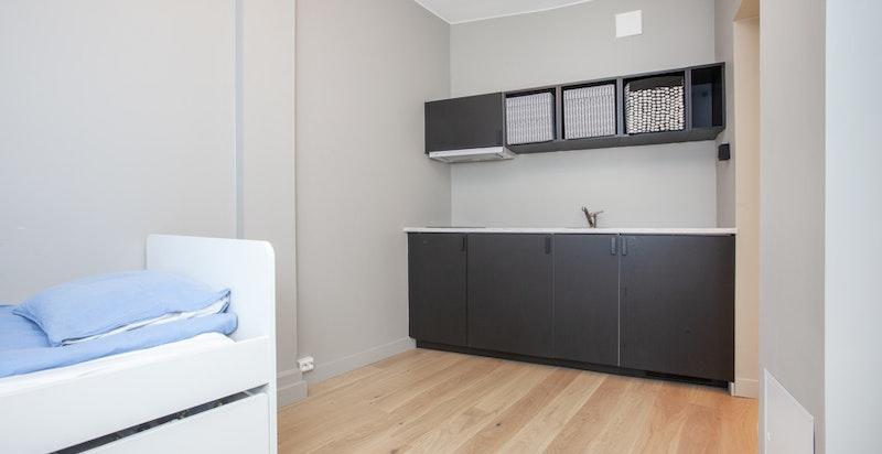 Kjøkkenet har servant, kjøleskap og platetopp