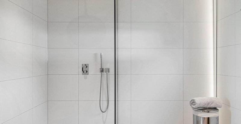 Badet er pent og det er lagt opp til mulighet for å montere et badekar til høyre for dusjvegg.