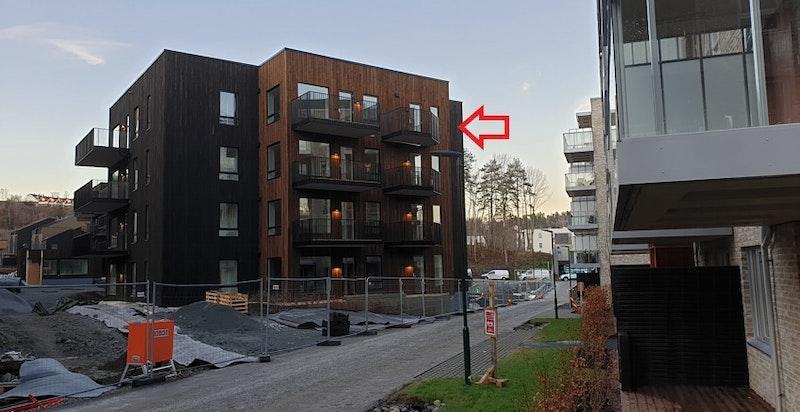 Rød pil illustrerer leilighetens beliggenhet i bygget