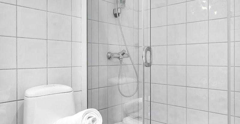Bad 2 inneholder dusjhjørne med skyvedør, sluk i dusj, toalett og servant med underskap