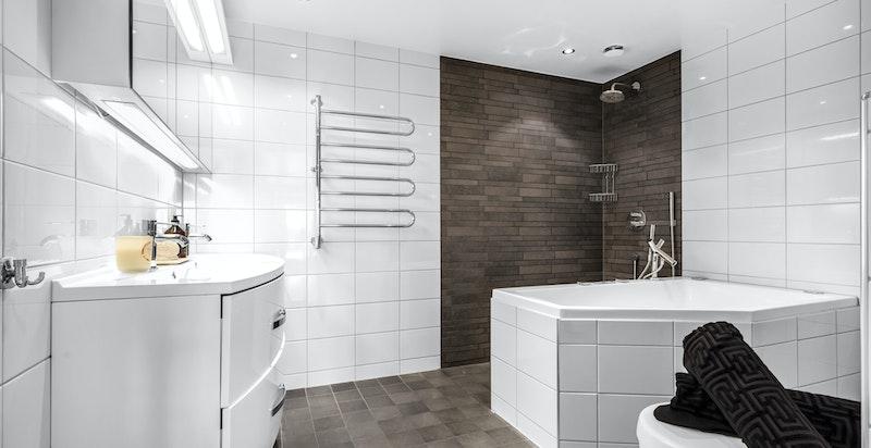 Pent hovedbad/wc med varmekabler i gulv. Badet inneholder dusjhjørne med sluk, boblebadekar med inspeksjonsluke i badekarfront, veggmontert toalett, to servanter med blandebatteri og underskap