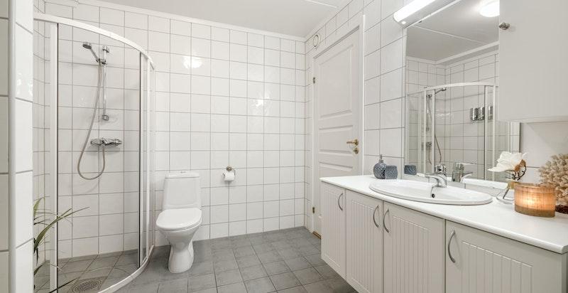 Romslig bad med egen vaskenisje, dusjhjørne og wc.