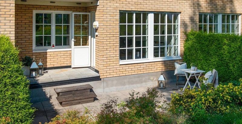 Nydelig og solrik uteplass foran leiligheten, skjermet med vintergrønn hekk og beplantning