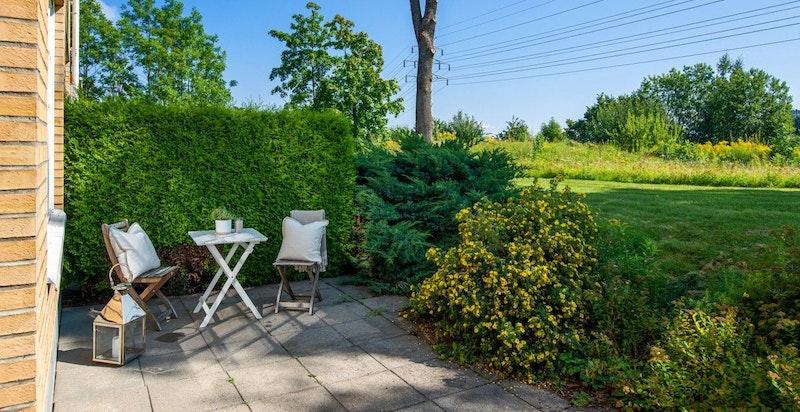 Hyggelig solrik uteplass foran leiligheten, skjermet med vintergrønn hekk og beplantning