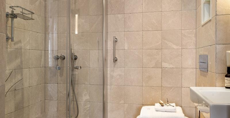 Bad 2 har veggmontert dusj med dusjvegger, klosett og servant.