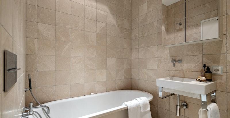 Bad 1 består av badekar, veggmontert klosett og servant.