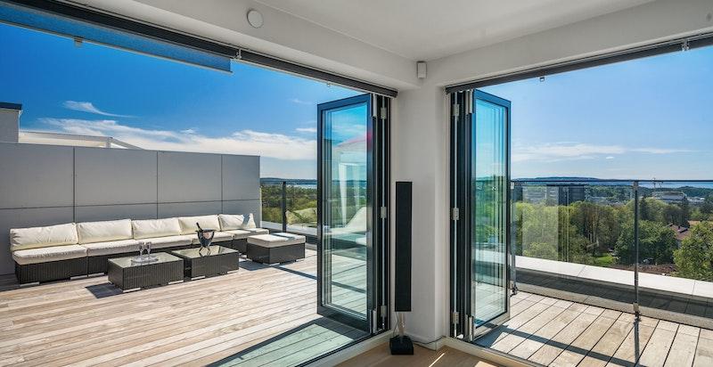 Et spektakulært ute / inne område på takterrassen når dørene åpnes helt opp