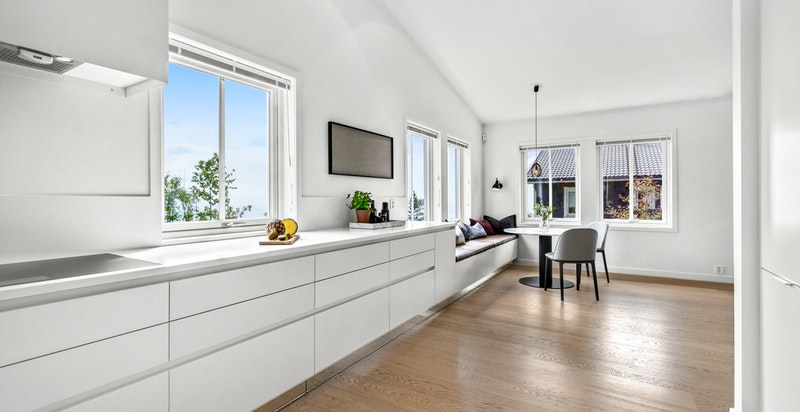 Innredningen på kjøkkenet består av glatte fronter med integrerte håndtak, Silestone benkeplate og bakplate i farge Iconic White.  Spesialtilpasset speilskjørt i overgang mellom gulv og kjøkken