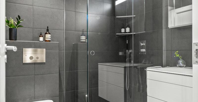 Meget pent flislagt bad med varmekabler i gulv og eksklusiv Keuco innredning. Badet inneholder dusjhjørne med spesialtilpassede dusjvegger som går fra gulv til tak med innfrest håndtak (levert av glassmester)