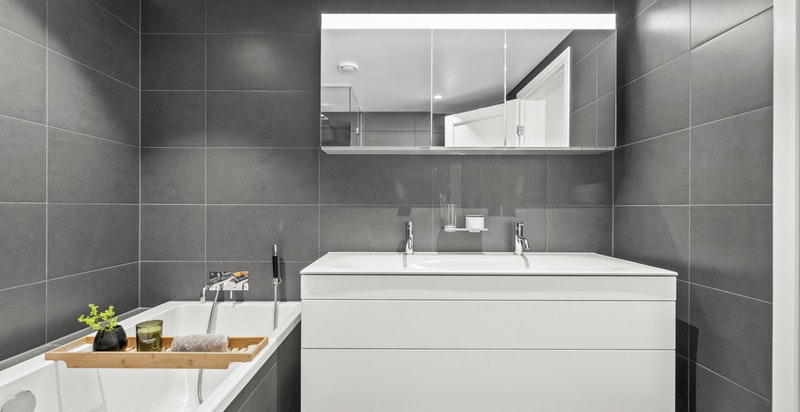 Badet inneholder innmurt badekar med flislagt front, dusjhjørne med spesialtilpassede dusjvegger som går fra gulv til tak med innfrest håndtak (levert av glassmester), veggmontert toalett. Det er ubenyttet el-punkt på vegg til evt. håndkletørker