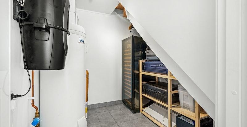 Dels under trapp er det en bod/teknisk rom/vaskerom med opplegg til vaskemaskin og tørketrommel