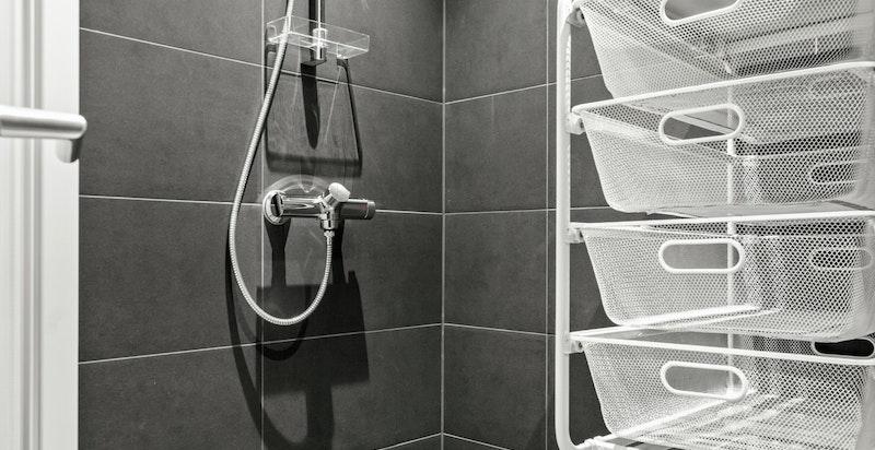 Badet er meget pent flislagt og inneholder dusjhjørne med sluk i gulv, veggmontert toalett, veggmontert servant med blandebatteri og ventil/avtrekk