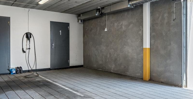 Det medfølger to åpne garasjeplasser (merket 1) i felles, lukket garasjeanlegg på sameiets eiendom