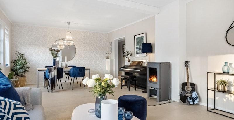 lys og luftig stue med peis, salongdel, spisestue og utgang til terrasse