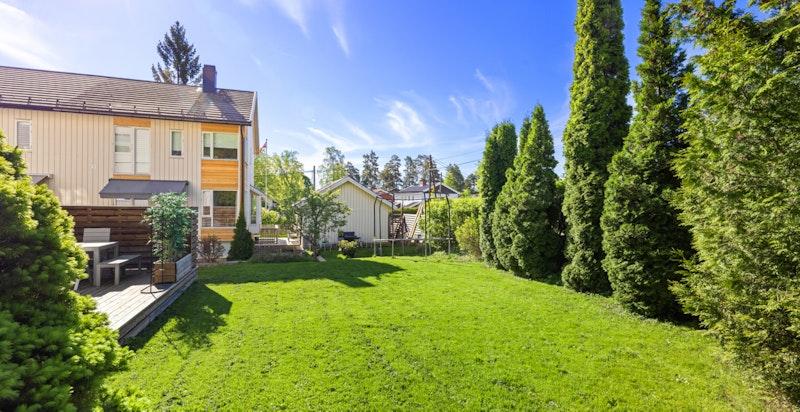 Flat og fin felles plen foran boligen og egen, seksjonert hagedel på siden av huset