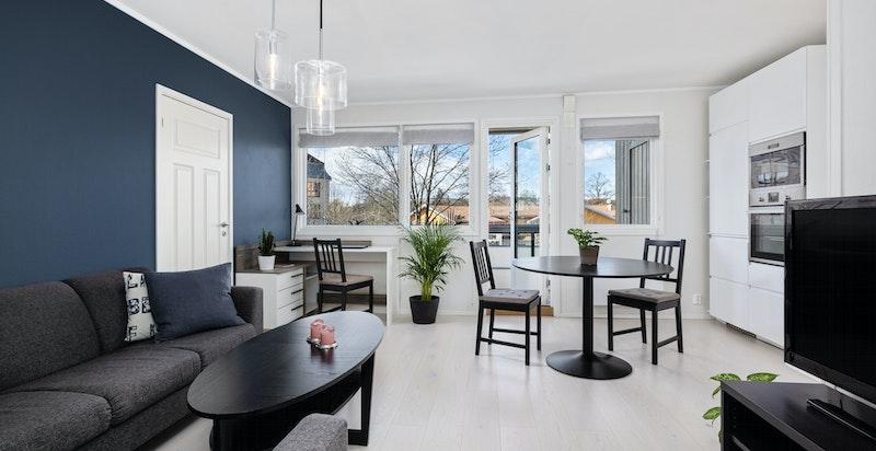Åpen stue med plass til både sittegruppe, TV-seksjon, kontor og spiseplass