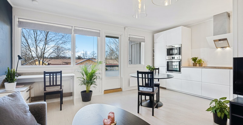 Åpen stue med godt lysinnslipp gjennom store vindusflater mot vest