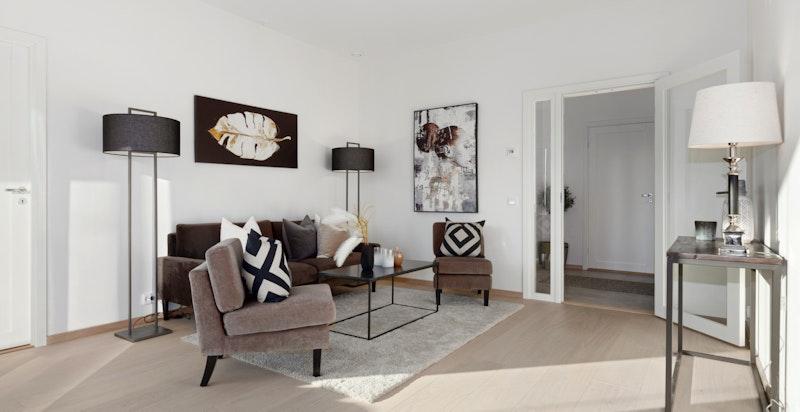 Den åpne planløsningen gir et fint og stort sosialt rom med plass til sittegruppe, lenestoler, TV-seksjon og øvrig møblement.