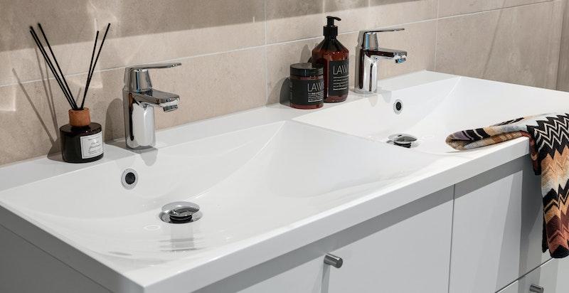 Stilrent bad med baderomsinnredning med brede skuffer, heldekkende dobbel vask og speilskap med tilpasset integrert lyst og stikkontakt.