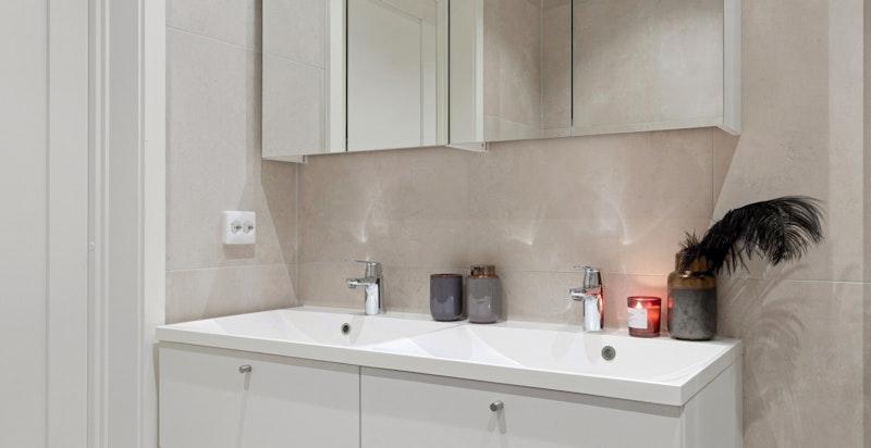 Dette badet har også dusjhjørne, vegghengt toalett og baderomsinnredning med brede skuffer og heldekkende dobbel vask med speilskap.