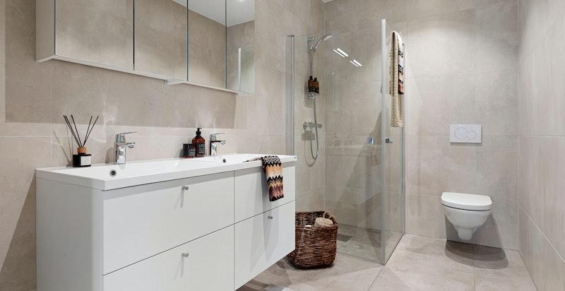 Fra hovedsoverommet er det inngang til eget bad med dusjhjørne og vegghengt toalett.