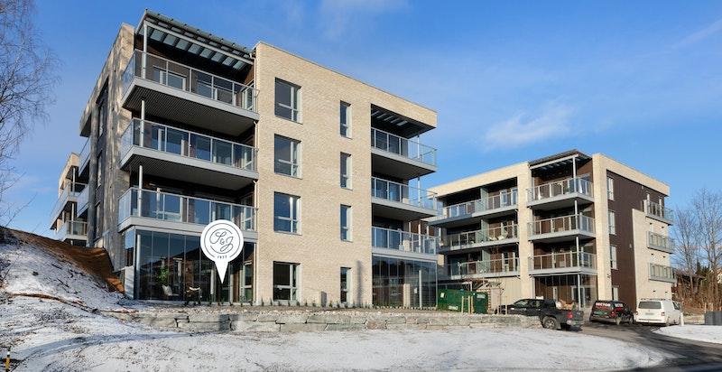 Nytt og moderne boligtun med fire punkthus beliggende på et platå hevet over gatenivå med grønne overganger mot omgivelsene. Moderne og lyse teglbygg med innslag av mørkt tre, glass og grått stål.