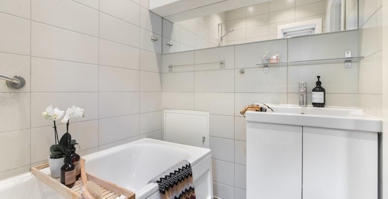 Flott bad/wc med badekar med dusjvegg, tilknyttet hovedsoverommet
