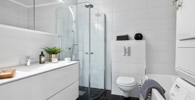 Flislagt baderom. Innebygget badekar og opplegg for vaskesøyle