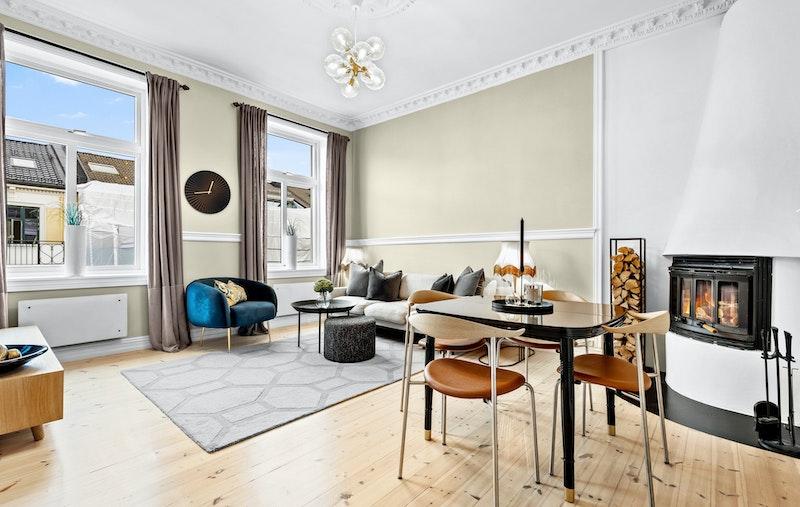 Lys og luftig stue med store vindusflater, mye himmel og hyggelig peisovn