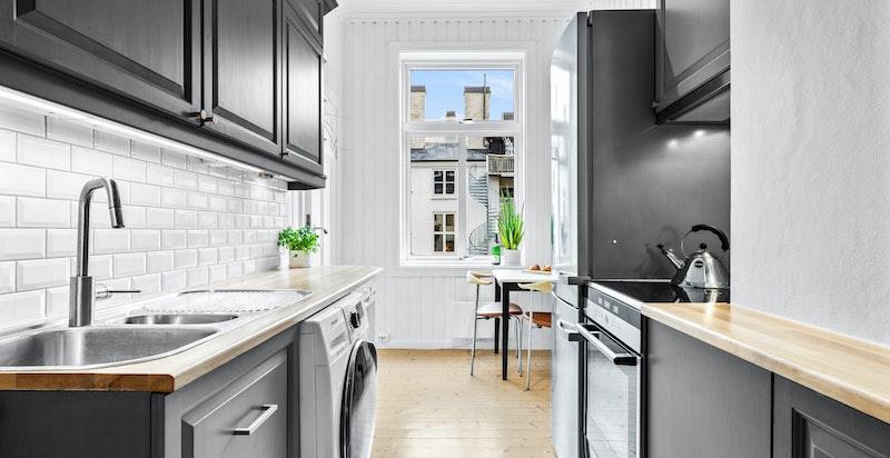 Kjøkkenet har godt med benkeplass- og oppbevaring. Vaskemaskin er plassert her.