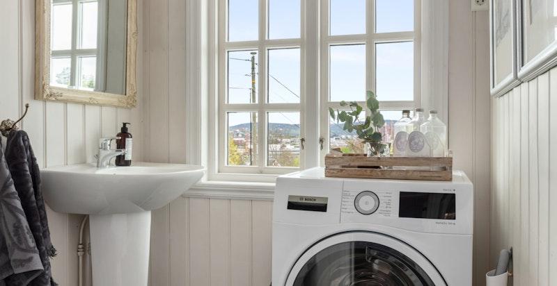 Praktisk toalettrom med wc, søyleservant og opplegg for vaskemaskin i boligens første etasje.