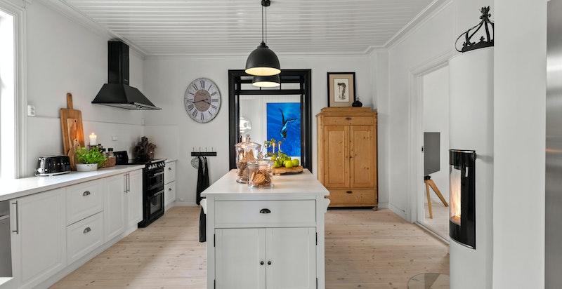 Malt kjøkkeninnredning med frittstående kjøkkenøy, malt heltre benkeplate og nedfelt porselenskum. Det er kullfiltervifte.
