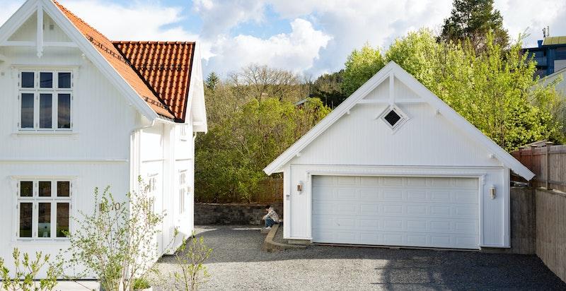 Boligen har parkering i dobbel garasje med oppbevaringsplass, samt trapp opp til hyggelig oppholdsrom