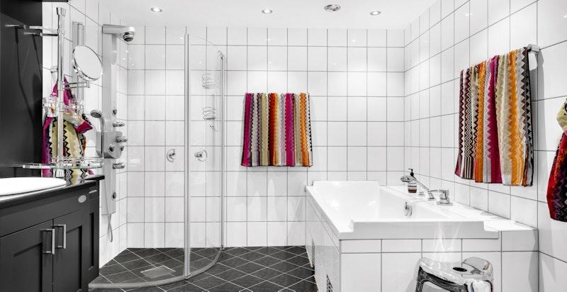 Et av boligens to bad. Pent flislagt i en tidløs fargekombinasjon.