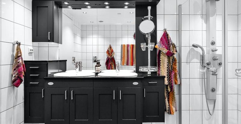 Badet er utstyrt med både badekar og dusj, to servanter og godt med skapplass.