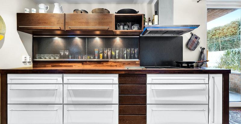Flott Sivesind kjøkken med integrerte hvitevarer med kjøl/frys, oppvaskmaskin, stekeovn, kaffemaskin induksjonstopp og et gasspunkt. Alle hvitevarer er fra Miele.