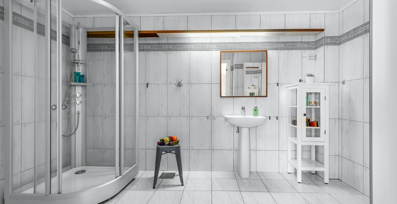 Badet inneholder søyleservant med blandebatteri, dusjkabinett, toalett, ventil i himling og sluk i gulv