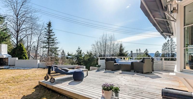 Usjenert terrasseplatting og plen. Hyggelig utepeis i enden av hagen
